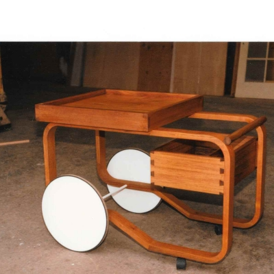 One of a pair in solid Teak and Teak veneer.   The wheels were later replaced with bicycle wheels.
