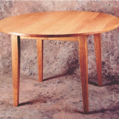 "42"" round solid cherry table which opens to hold 2 18"" leaves."