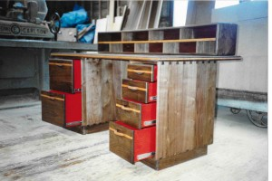 walnut desk with red drawers.